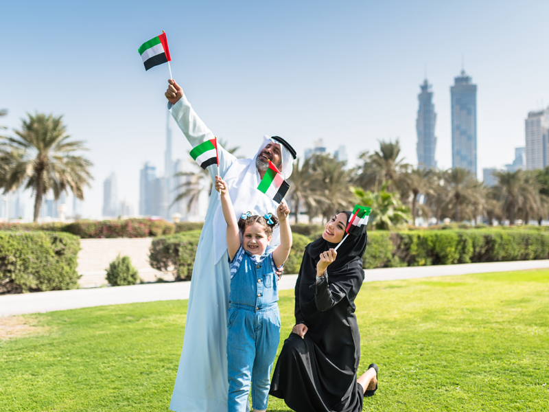 An Emirati family waving flags celebrates UAE National Day